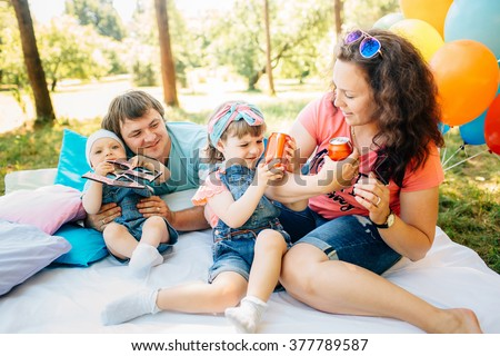 Young family with childs having picnic with pillows and colored balloons outdoors. Parents with two children relax in a sunny summer garden. Mother, father, little girl and baby boy playing in park.