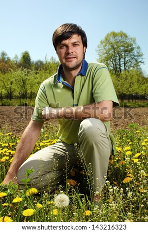 Young farmer knelt near his land in a sunny day
