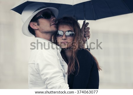 Young fashion couple in love with umbrella on city street