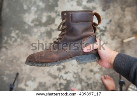 Young fashion man hand with brown leather boot.