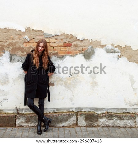 Young fashion sensual woman posing on the street near old brick wall background in black coat feels sad and alone depressed photo