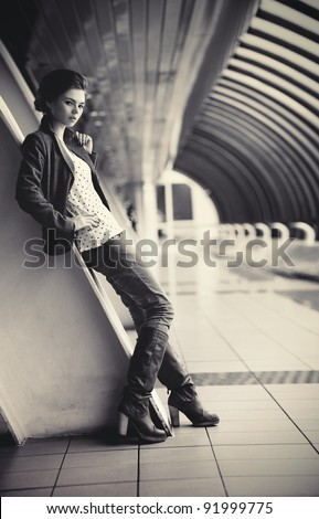 Young fashion woman in modern tunnel. Film style colors.