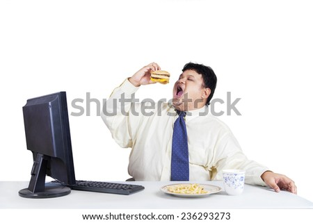 Young fat businessperson working with computer while eating fast food, isolated on white