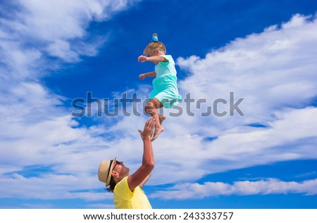 Young father and little daughter have fun on the beach