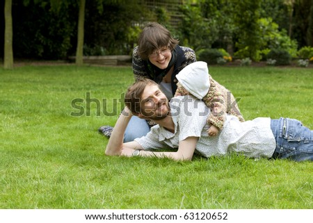 Young father lying in grass having fun together with his family