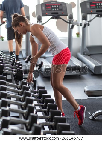 Young female at the gym using dumbbels