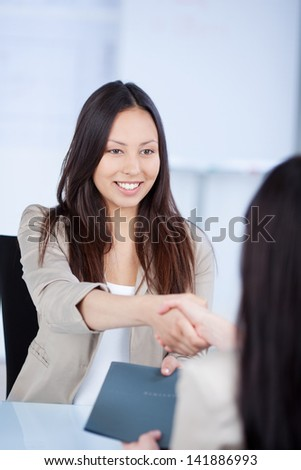 Young female candidate shaking hands with businesswoman at office desk