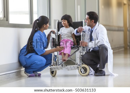 Young female child patient in wheelchair sitting in hospital corridor with Indian Asian female nurse and male doctor