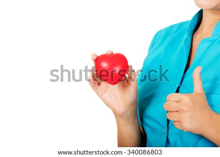 Young female doctor or nurse holding heart toy.