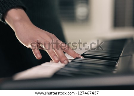 Young female practicing with piano. Closeup. Selective focus on hand