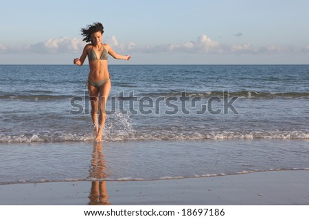 Young female running out of the sea