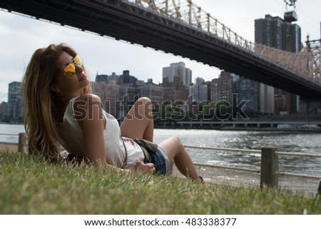 Young female smiling while relaxing on the grass below the Queensboro bridge on Roosevelt Island, New York City