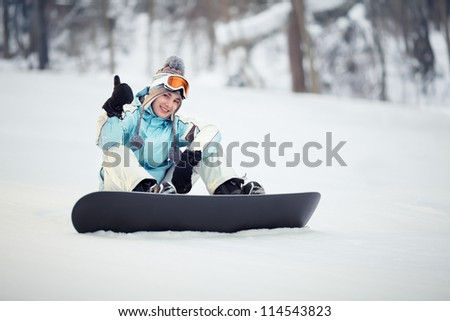 Young female snowboarder sitting on slope and showing thumb up