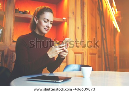 Young female student is chatting on mobile phone with friend while sitting in modern library interior, gorgeous Caucasian woman using cell telephone while rest in coffee shop during winter holidays