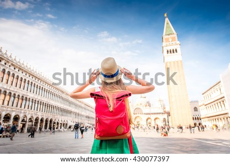 Young female traveler with hat and backpack standing on San Marco square with tower and basilica on the background in Venice. Back view