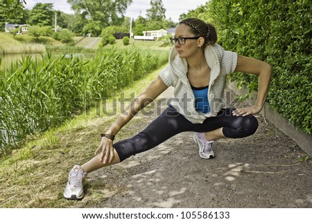 Young fit woman is stretching her legs