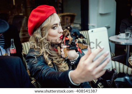 Young french beautiful girl with a small dog taking selfie in a Parisian street cafe