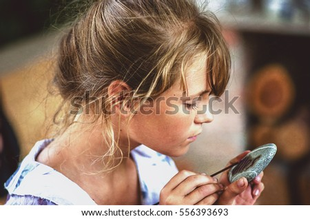 young girl artist painting with oil paints on the stone