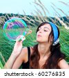 Young girl blowing a big soap bubble - stock photo