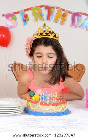 Young girl blowing birthday candles