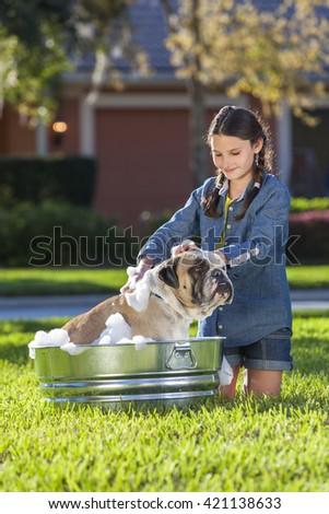 Young girl child washing her pet dog, a bulldog, outside in a metal tub