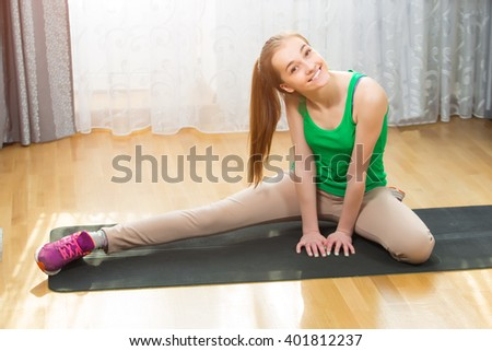 Young girl doing morning workout in bright room
