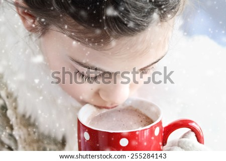 Young girl dressed warmly, drinking hot chocolate outdoor in the winter. Selective focus on child's eyes with extreme shallow depth of field.