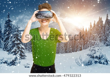 Young girl getting experience VR headset glasses, is using augmented reality eyeglasses, being in a virtual reality, on the hillside, in winter in the sun