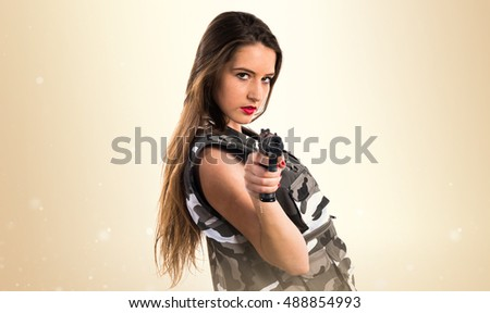 Young girl holding a pistol over ocher background