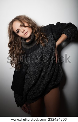 Young girl in a long sweater men standing at the wall