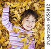 Young Girl in a Pile of Autumn Leaves - stock photo