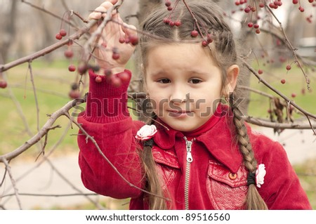 young girl in autumn park, in red coat