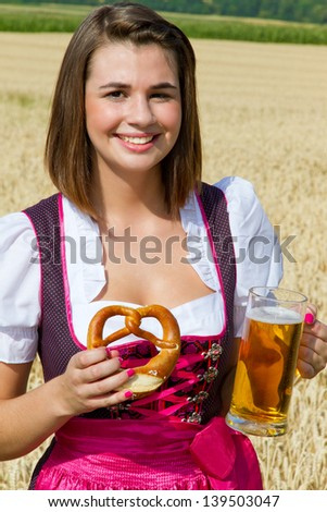 Young girl in dirndl with bear and pretzel