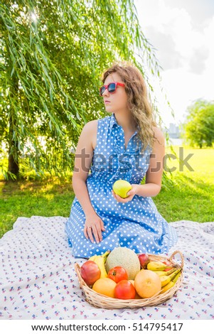 Young girl in dress and red sunglasses sitting on picnic blanket holding green apple in front of fruit basket
