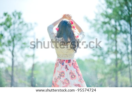 Young Girl in Red Flower Dress Standing Facing Sun From Back