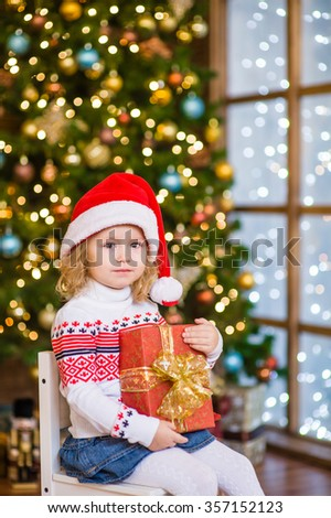 Young girl in red santa hat sitting with big gift box near the Christmas tree