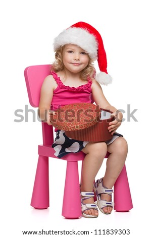 Young girl in santa hat opening gift box