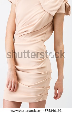 Young girl in short beige dress on the white background