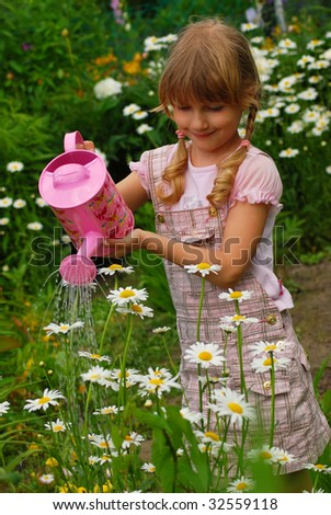 young girl in the garden with pink watering can