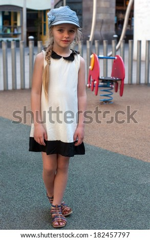 Young girl in white dress and denim cap on the playground
