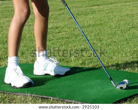 Young girl in white shoes standing on a practicing mat during golf lesson, holding a golf club