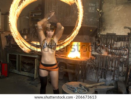 Young girl juggles with fire in this smithy