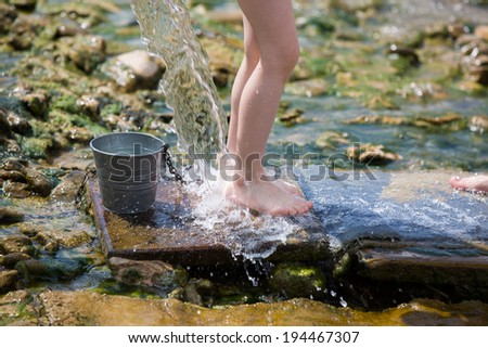 young girl legs under pure water stream