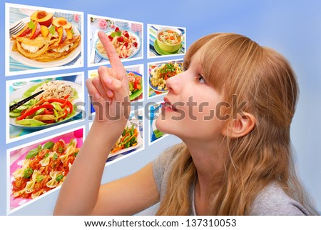 young girl pointing the finger up on touch screen with lunch`s pictures and choosing the best one