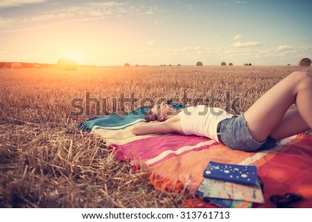Young girl relaxing on the cover in the field at sunset