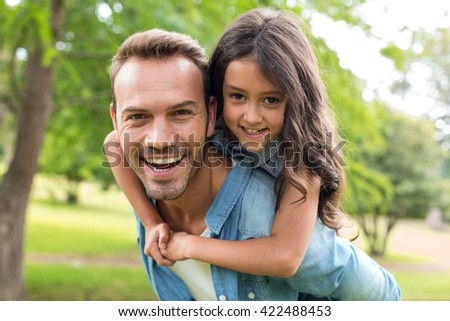 Young girl rides piggyback on her fathers shoulders in the park