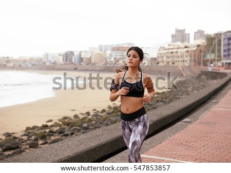 Young girl running on path with a cityscape behind her and a beach to her right wearing casual clothes and her hair tied back
