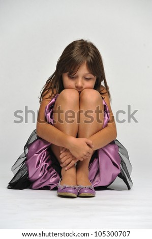 Young girl sitting on the floor hiding her face behind her knees looking down