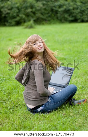 Young girl sitting on the grass with laptop