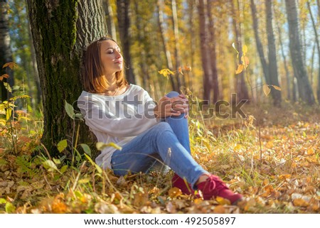Young girl sitting under a tree in the forest, sunny autumn day. Unity with nature, relaxation and enjoyment